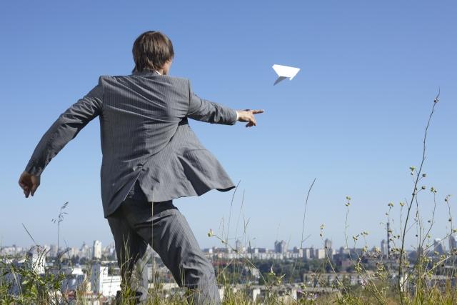 紙飛行機と男性
